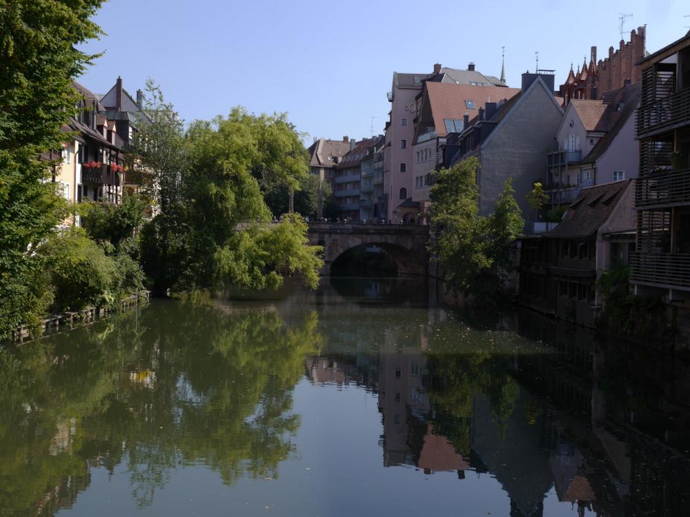 Eine Stadtlandschaft an der Pegnitz in Nürnberg. Man sieht die Pegnitz, rechts und links sind dicht am Wasser Häuser und in der MItte eine Brücke, man sieht aber auch viele grüne Bäume. Die Bäume und Häuser spiegeln sich im Wasser.