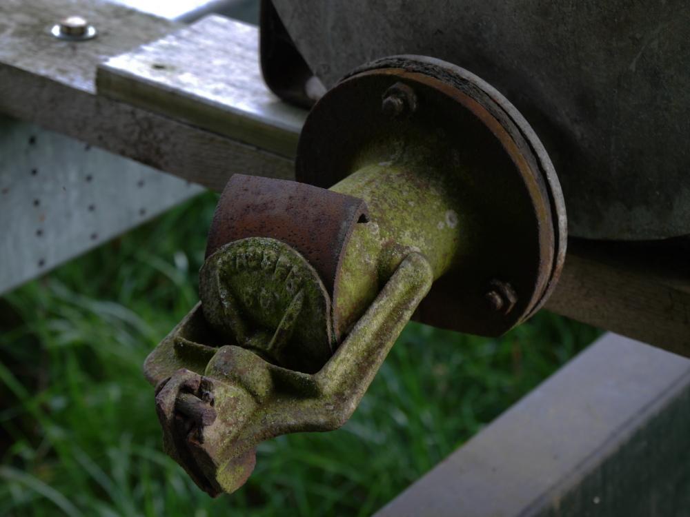 """Das Foto zeigt den verrosteten und teilweise bemosten Ausslass aus einem alten, landwirtschaftlichem Wasserfaß. Auf dem Verschluß kannman die Aufschrift """"Mauser 66"""" erkennen."""