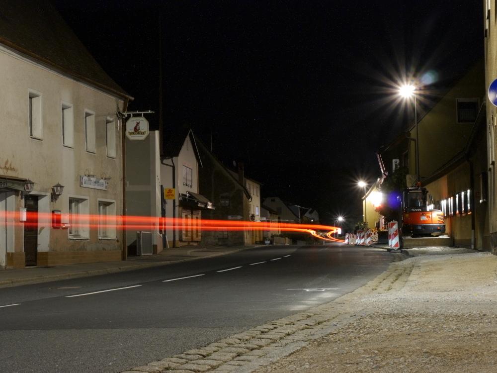 Das Foto zeigt eine Nachtaufnahme an der Hauptstraße in einem Dorf, man sieht geschlossene Geschäfte und rechts ist eine Baustelle mit einem Bagger. Ein Auto ist durch die Baustelle gefahren und man sieht durch die lange Belichtungszeit die Rücklichter als rote Streifen.