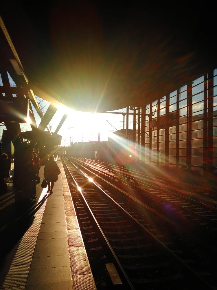 Das Foto zeigt eine Gegenlichtaufnahme an einem Bahnsteig, auf der linken Seite ist der Bahnsteig, auf dem man auch die Silouetten von Menschen erkennen kann. rechts sind drei Gleise und dann die Außenwand der Bahnhofshalle. Man blickt direkt in Richtung der Sonne, deren strahlen das ganze in ein seltsames, etwas unwirkliches Licht tauchen. In den blanken Schienen spiegelt sich die Sonne. Das Foto ist ein Farbfoto.