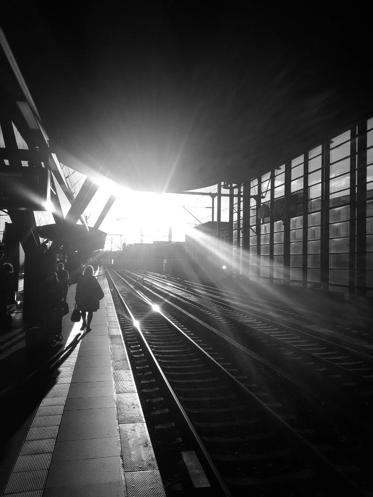 Das Foto zeigt eine Gegenlichtaufnahme an einem Bahnsteig, auf der linken Seite ist der Bahnsteig, auf dem man auch die Silouetten von Menschen erkennen kann. rechts sind drei Gleise und dann die Außenwand der Bahnhofshalle. Man blickt direkt in Richtung der Sonne, deren strahlen das ganze in ein seltsames, etwas unwirkliches Licht tauchen. In den blanken Schienen spiegelt sich die Sonne. Das Foto ist ein Schwarz-Weiß-Foto.