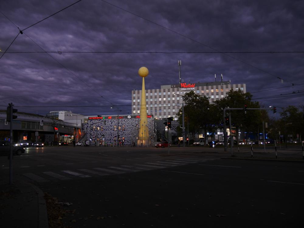 Das Foto zeigt eine Straßenszene in Wien am Einkaufszentrum in Kagran. Die Aufnahme ist abends entstanden, die Beleuchtung ist schon eingeschaltet und es sind sehr dunkle Wolken am Himmel, die zu einem dramatischen Eindruck führen. Derzeit stehen die meisten Autos auch an roten Ampeln, daher ist der große Platz in der Mitte gerade frei. Vor dem Einkaufszentrum steht auch noch eine große, goldene Metallskulptur in Form eines Kegels mit einer Kugel an der Spitze.