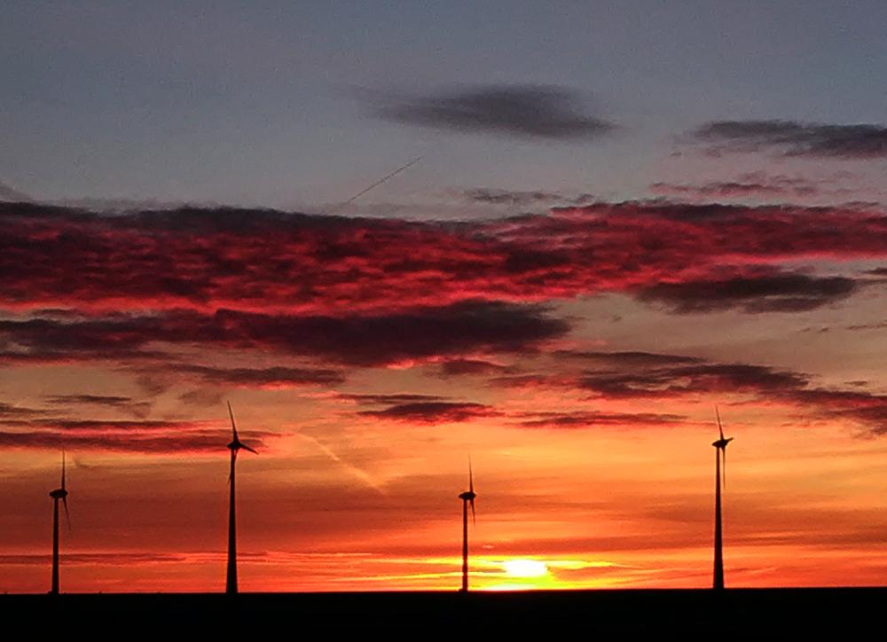 Eine Landschaftsaufnahme von einem Sonnenuntergang. Man sieht in der Landschaft vier Windkraftanlagen, hinter denen geht die Sonne auf. Am Himmel sind leichte Wolken, das Bild ist durch die Sonne und ihr orangenes Licht dramatisch eingefärbt.